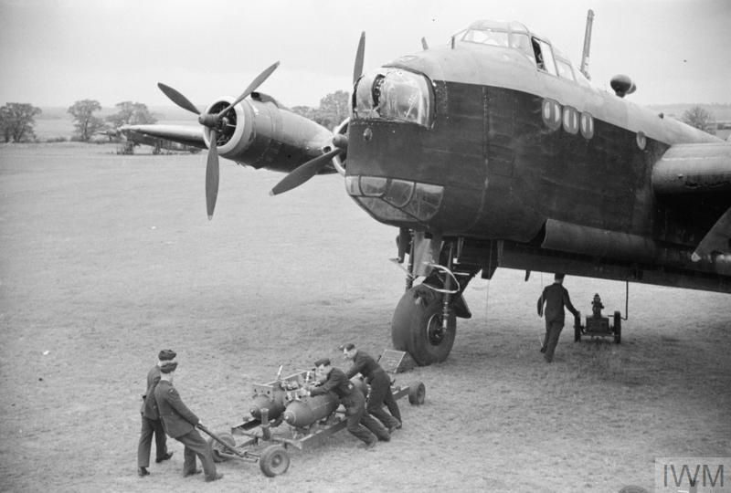 A Stirling I of No 218 (Gold Coast) Squadron being bombed-up at Downham Market, Norfolk, in the summer of 1942, soon after the airfield, which was a satellite of Marham, opened. The bomb train has arrived at the Stirling's dispersal and a pair of 1,000lb GP bombs are about to be pushed into position beneath the aircraft. © IWM (D 8972)
