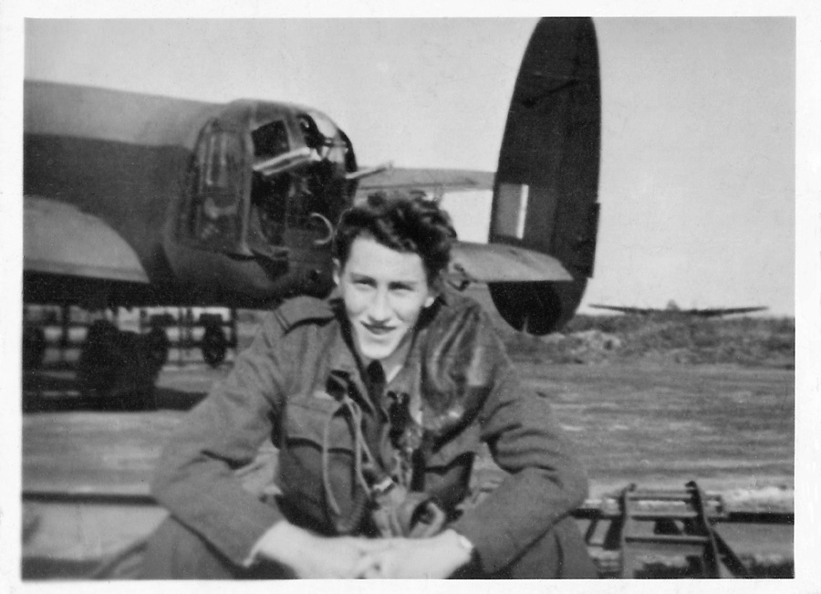 Fg Off. Niels Erik Westergaard, DFC, sitting in front of a Lancaster at an unknown air station. (Author's collection)