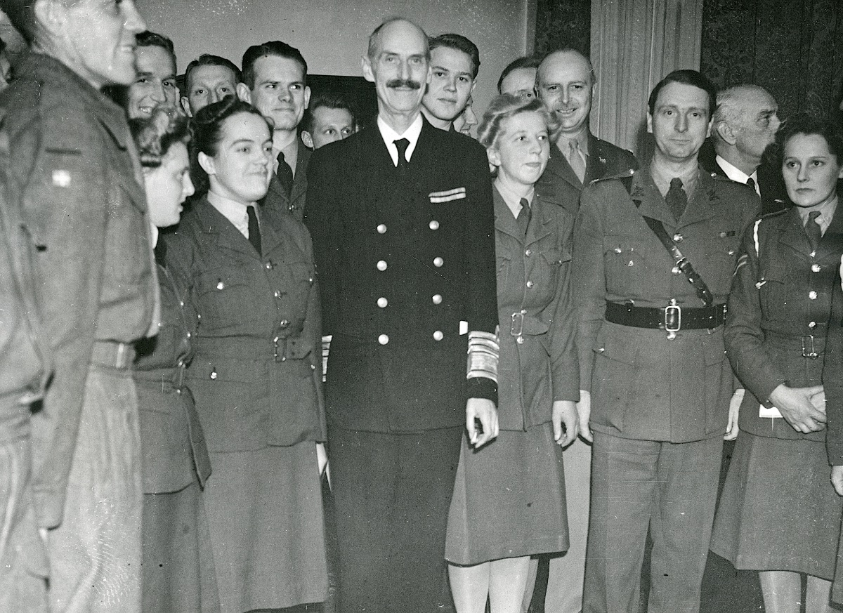 Photo taken in the Danish club at the celebration of King Christian X's 73rd birthday. Magda Marie Andersen is standing next to King Haakon VII of Norway, and Karen Andersen is standing next to Magda. The photo also include two Danish RAF-pilots, Jørgen Herner Petersen looking over the King's shoulder, and an unidentified volunteer standing between the King and Magda. Second from the right is Maj. Eyvind Knauer, who was in charge of the Recruiting Office, Danish Nationals from July 1943 to May 1944. Looking over his right shoulder is Lt Col Helge William Spange (O-0276655), US Army. (Museum of Danish Resistance)