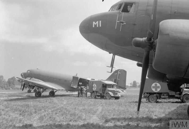 A casualty from the fighting in Normandy is loaded from an Army ambulance into one of the Douglas Dakota Mark IIIs of No. 46 Group at B2/Bazenville, Normandy, for evacuation to the United Kingdom.