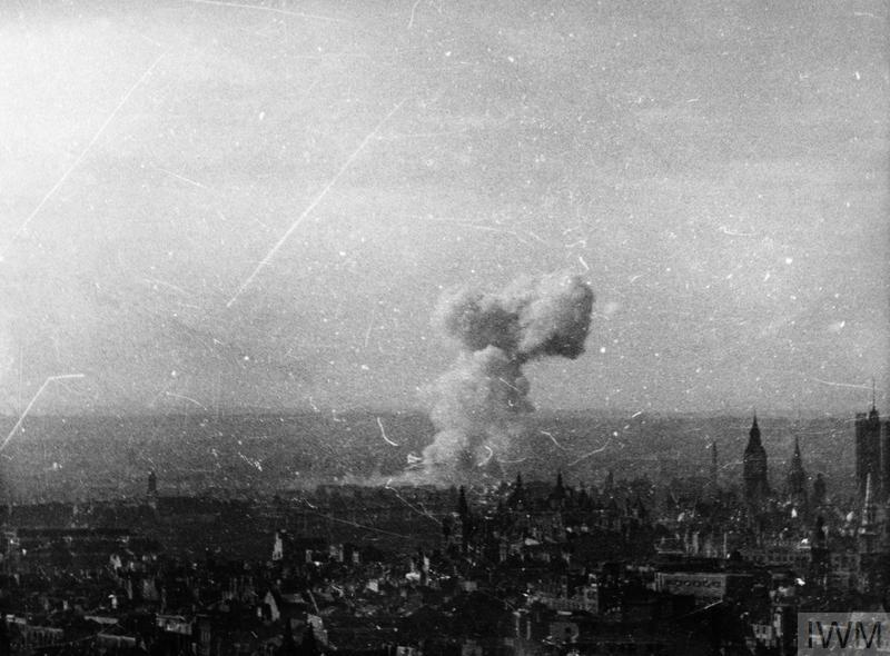 A view over the rooftops of London captured on cine film as a V1 flying bomb explodes close to Westminster in London. Big Ben and the Houses of Parliament can be seen on the right. © IWM ([MOI] FLM 2000)